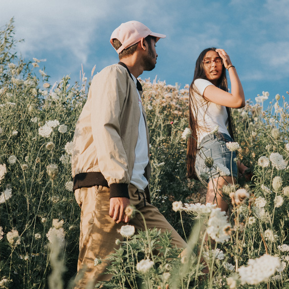 Man and woman looking at each other in a flower field
