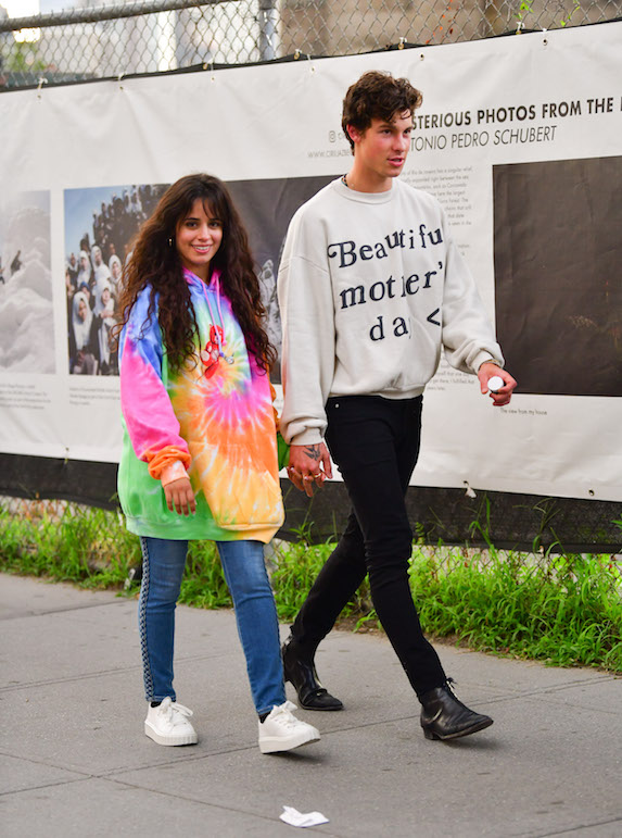 Camila Cabella wears a tie-die hoodie and jeans as she walks with boyfriend Shawn Mendes