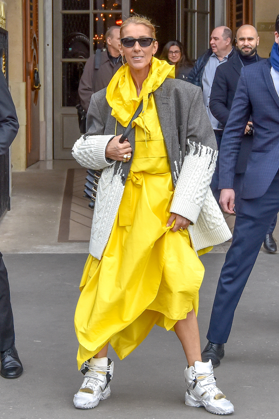 Celine Dion wears a yellow dress and grey oversized blazer with chunky hi-top sneakers
