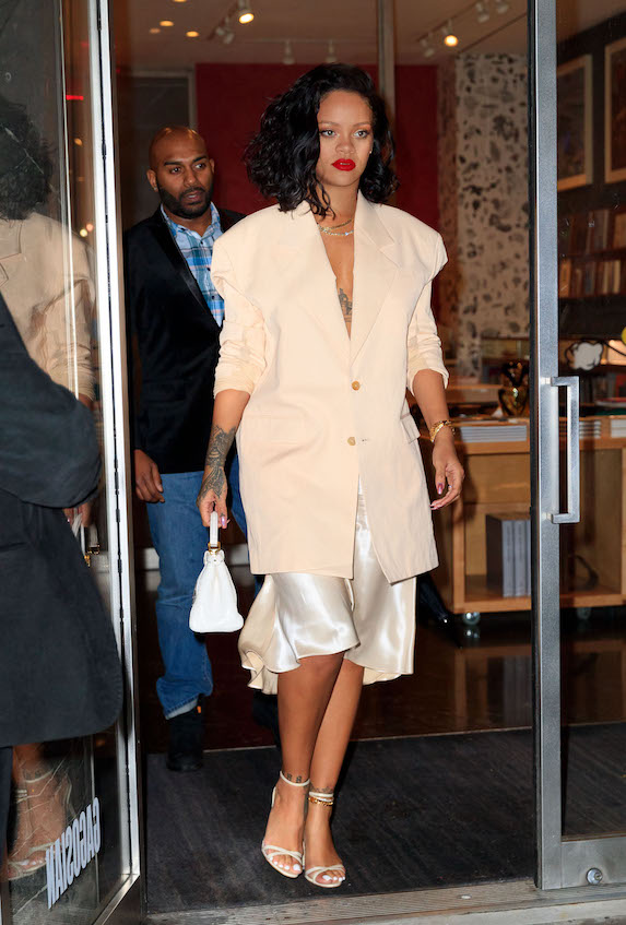 Rihanna wears an oversized cream blazer with satin slip skirt