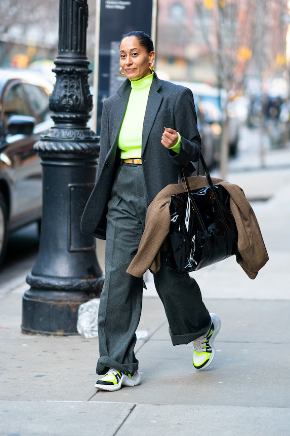 Tracee Ellis Ross wears a grey pants suit, neon shirt and chunky sneakers