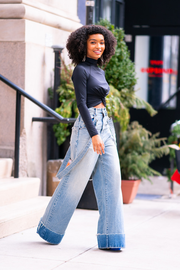 Yara Shahidi wears a black crop top and oversized, wide-leg jeans