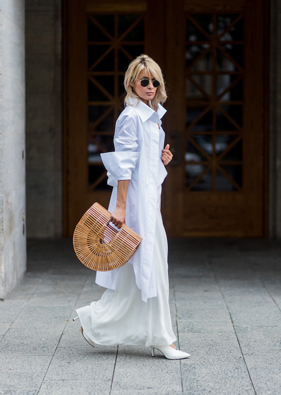 Model Gitta Banko wears a white outfit and accessorizes with a Cult Gaia bamboo bag
