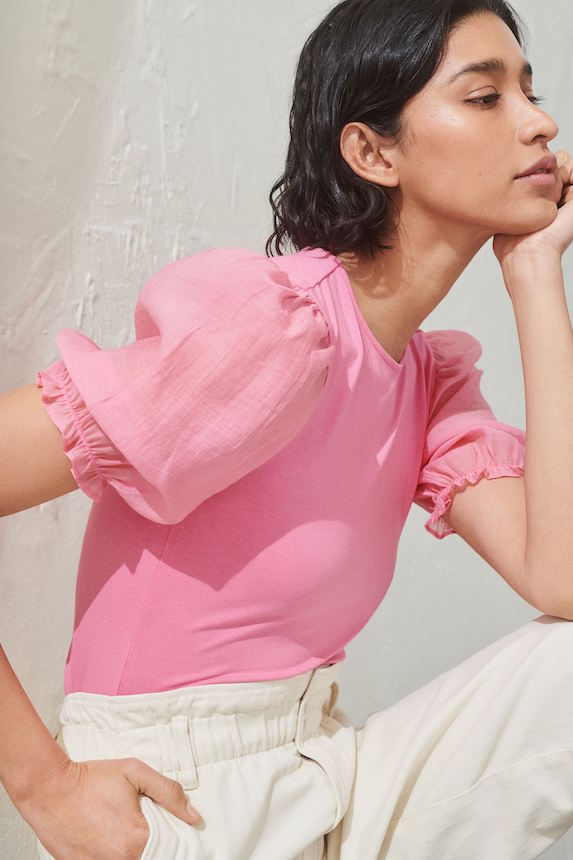 Model wears a pink shirt with voluminous sleeves