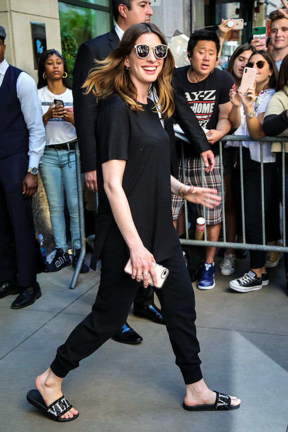 Anna Hathaway wears a black tee, pants and striped slide shoes