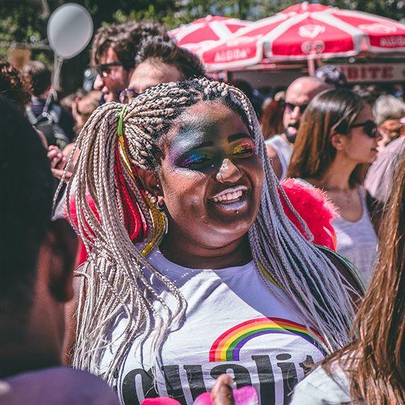 Woman at a pride parade with rainbow makeup