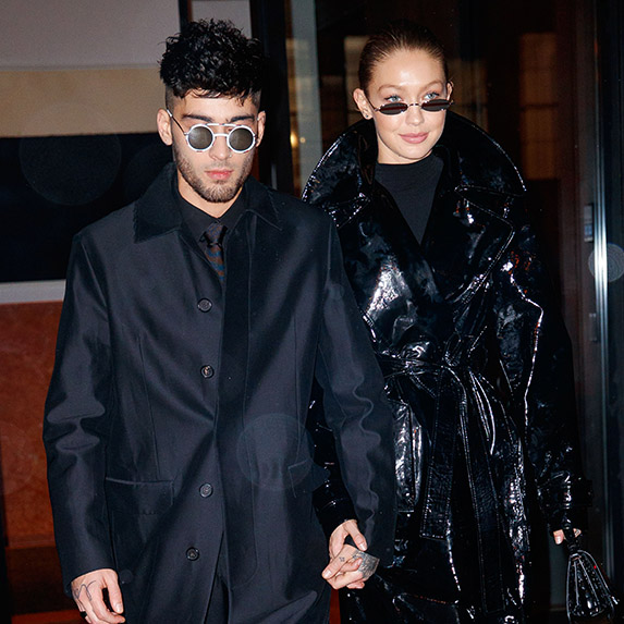 Gigi Hadid and Zayn Malik walking hand-in-hand in matching all-black outfits and sunglasses