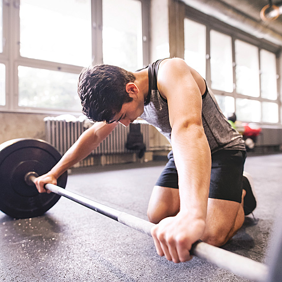 Tired man struggling to lift barbell