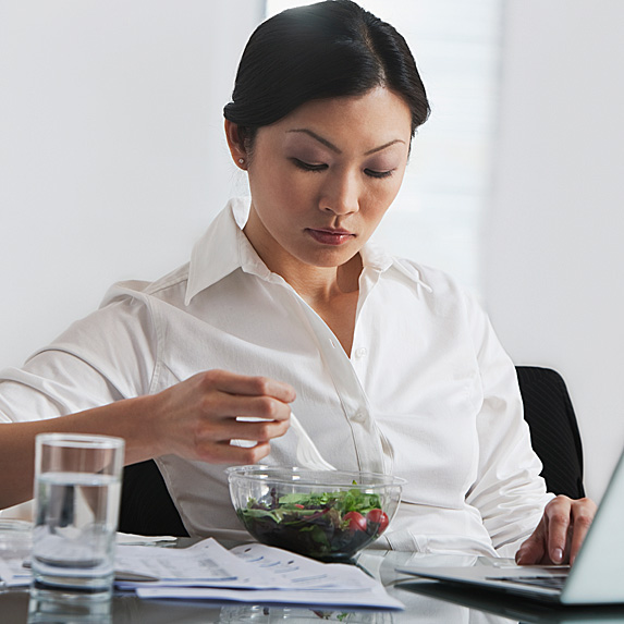 Woman sitting at desk eating a salad with glass of water next to her