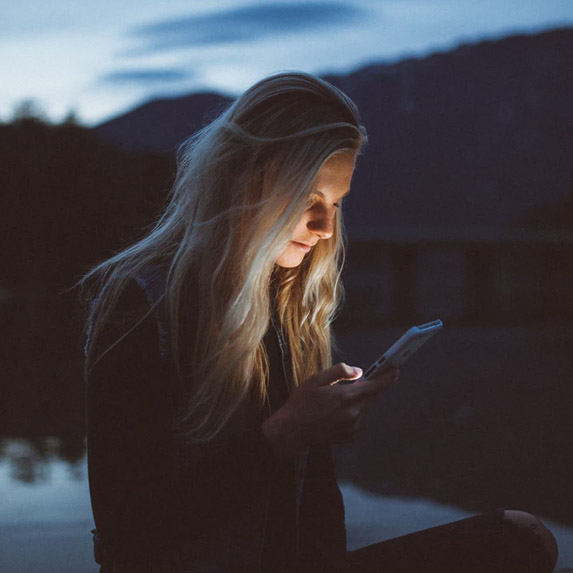Woman sits alone outside on her phone