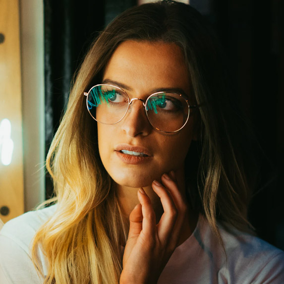 Girl in glasses looks out a window, towards the light