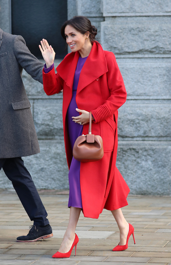 A pregnant Meghan Markle wears a purple dress, red coat and matching heels in 2019