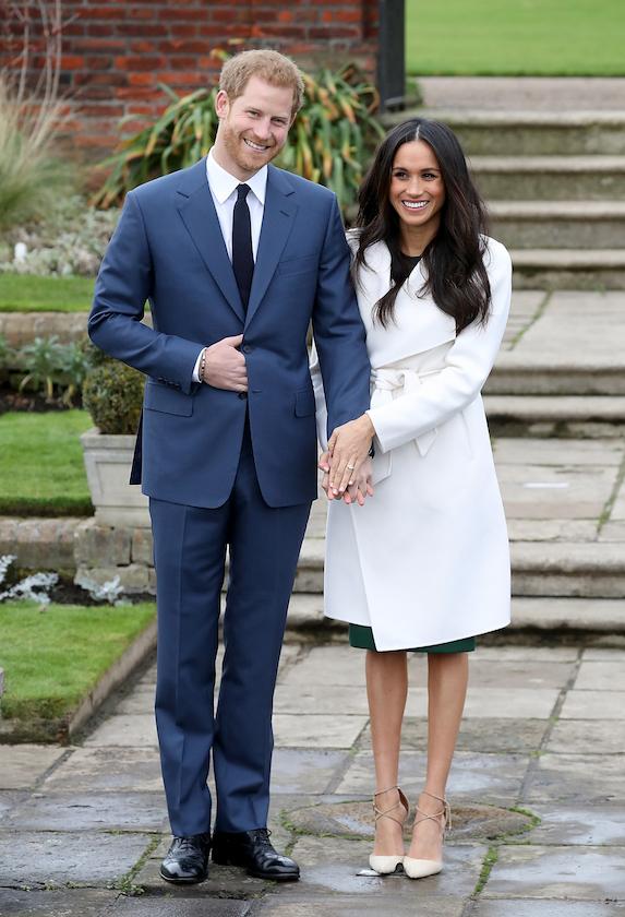 Meghan Markle wears a white overcoat as she stands alongside her then-fiancée, Prince Harry in 2017