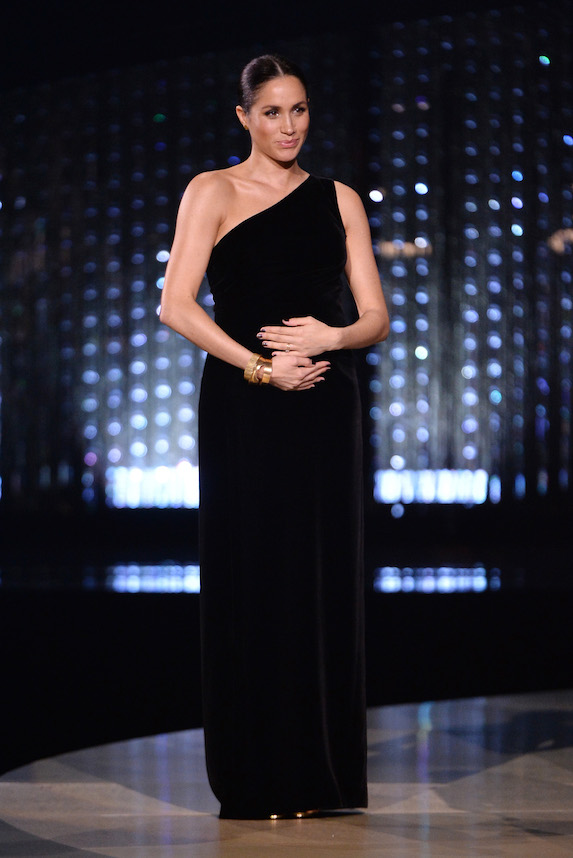 A pregnant Meghan Markle wears a one-shoulder black gown at the Fashion Awards in 2018