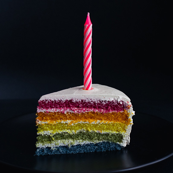 Slice of rainbow cake with one pink candle on top