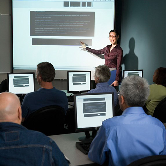 A woman teaching a class in front of computer screens