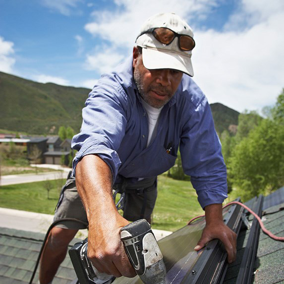 A man doing work on a house roof