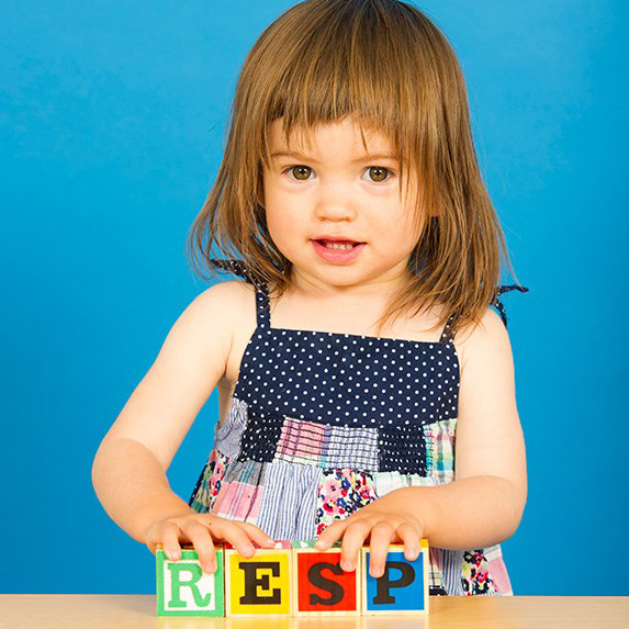 a little girl spelling RESP with blocks