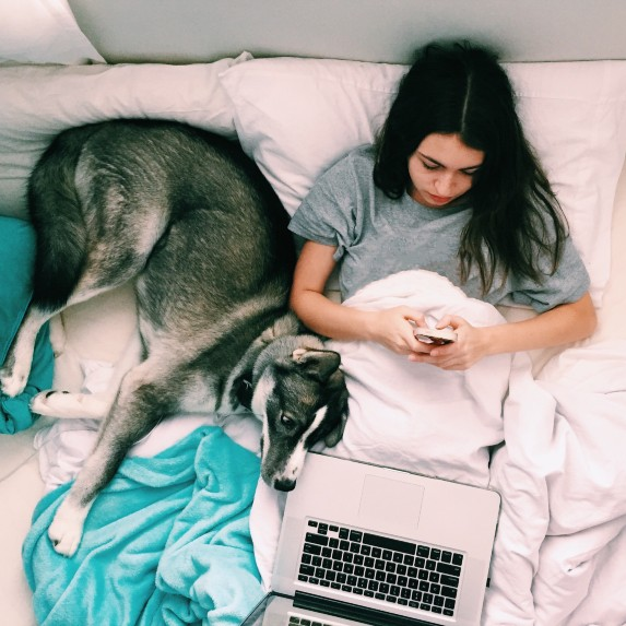 woman in bed with dog and phone