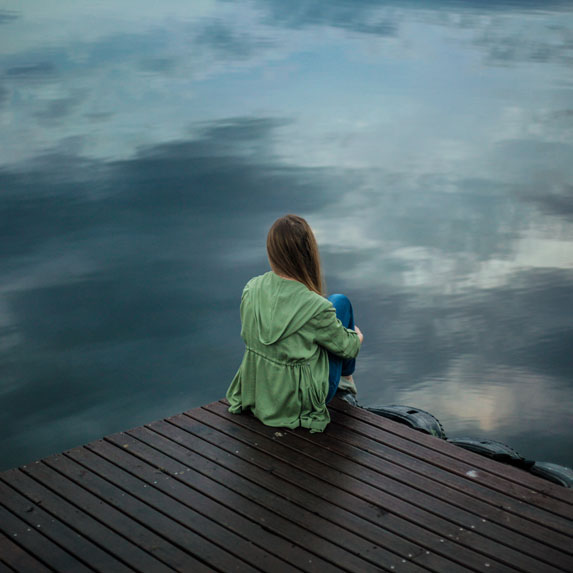 woman sitting alone on the dock