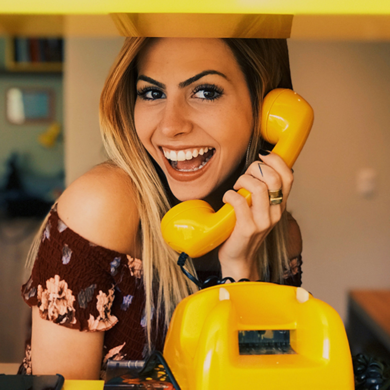 Woman holding a yellow rotary phone and smiling cheekily