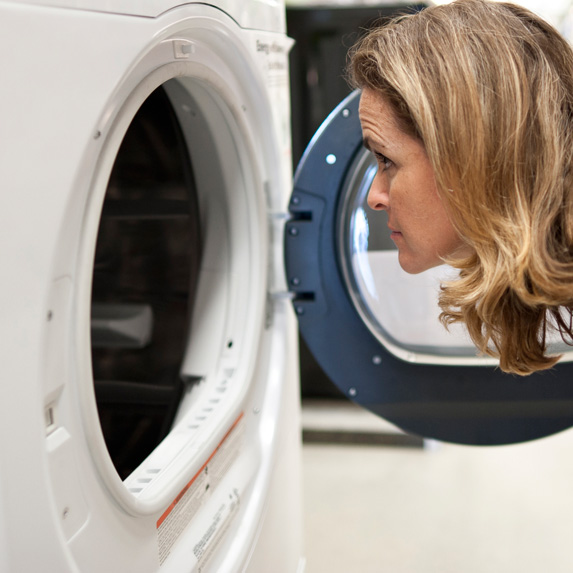 Woman looking into dryer