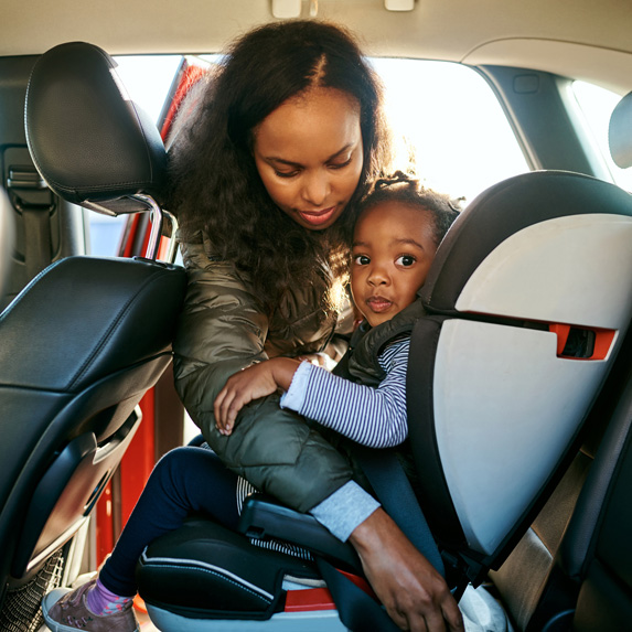 Mother putting child into car seat