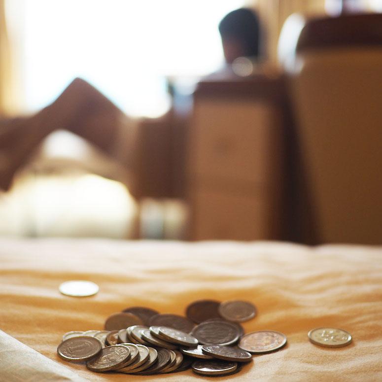 Coins lying on a bed with person in background