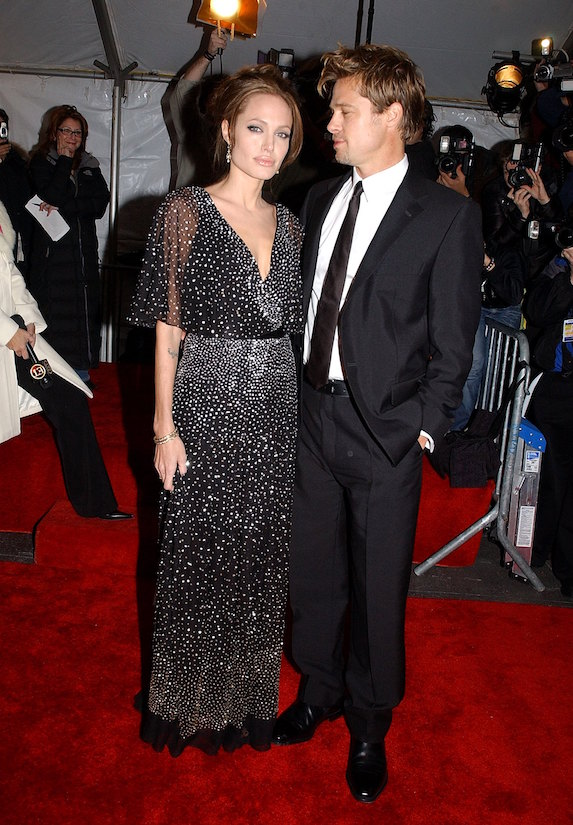 Angelina Jolie wears a black wrap-style gown as she stands alongside Brad Pitt