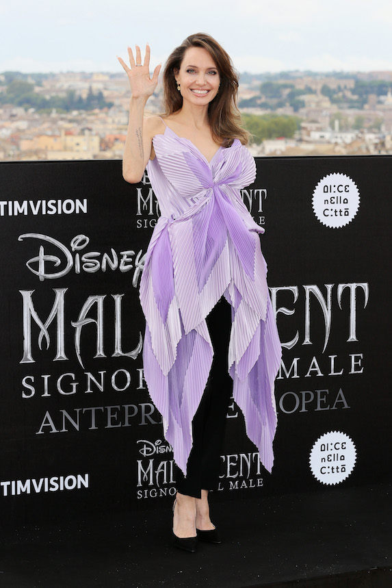 Angelina Jolie wears a pleat-detail purple top with black pants to a photo call in Rome in 2019