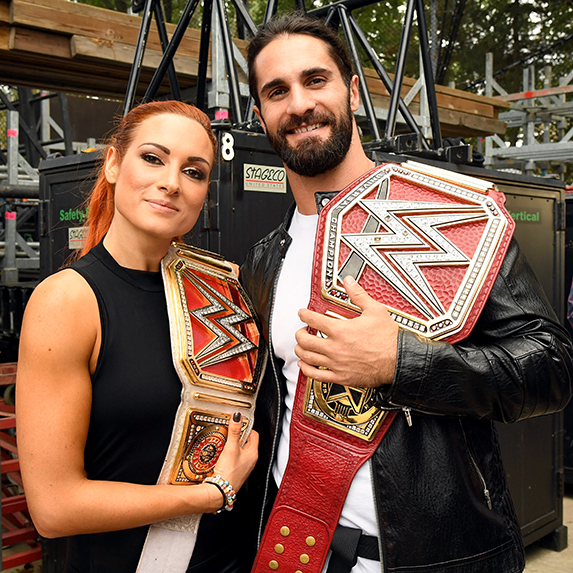 Becky Lynch and Seth Rollins standing with their WWE belts