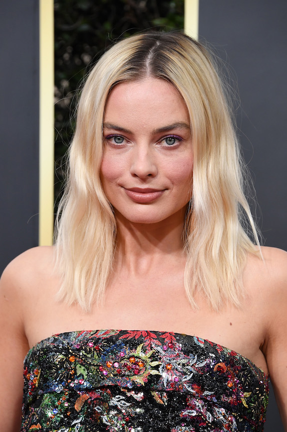 Margot Robbie wears her hair platinum blonde with deep roots