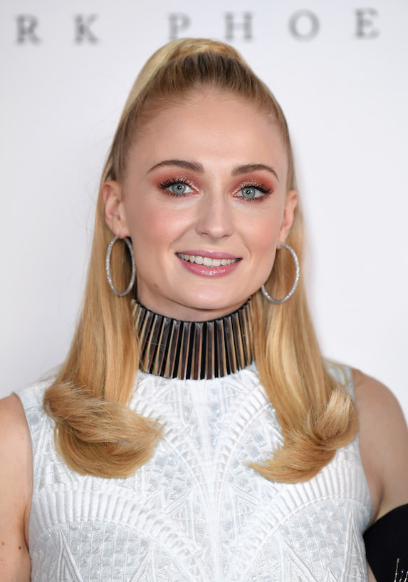 Sophie Turner wears her hair in a half-up style, with the ends flipped