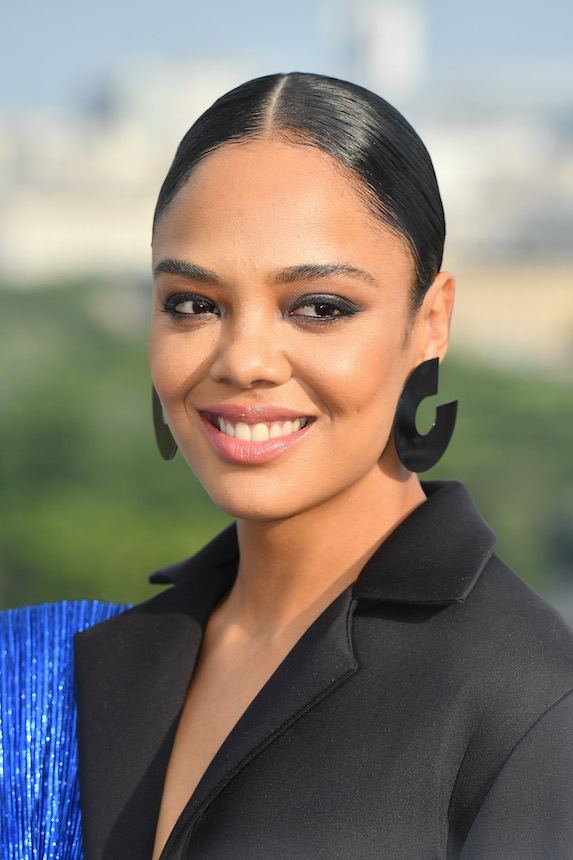 Actress Tessa Thompson wears her hair in a low bun with a center-part