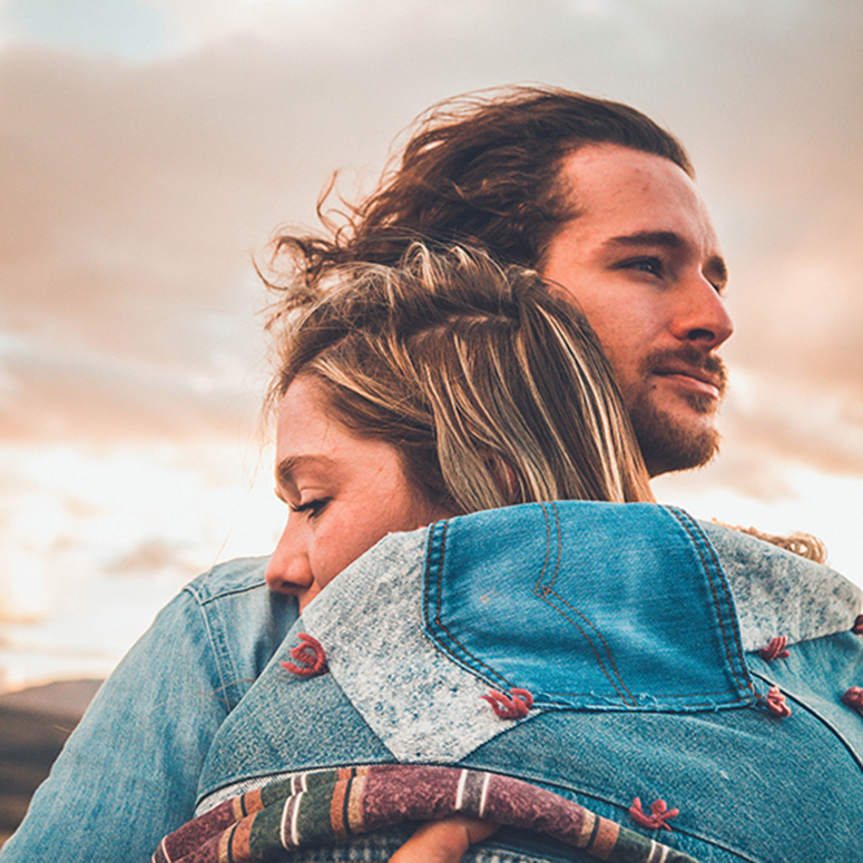 woman leaning into man for hug and comfort