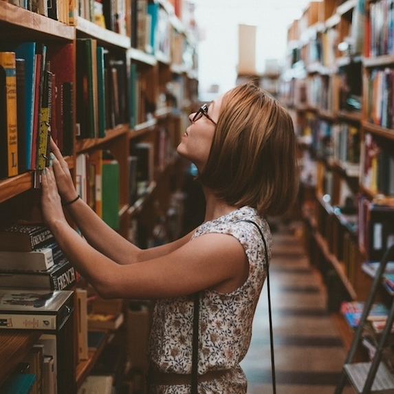 A person in the library grabbing a book from the shelf