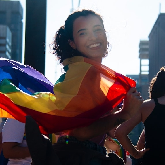 A person wrapped in a rainbow flag at a parade