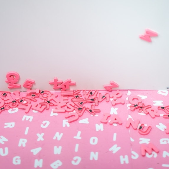 Random pink and white letters from the alphabet