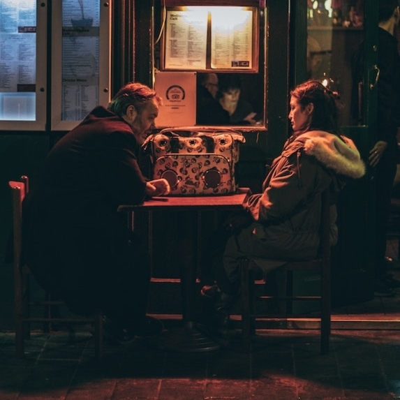 Couple sits together unhappily at a restaurant table