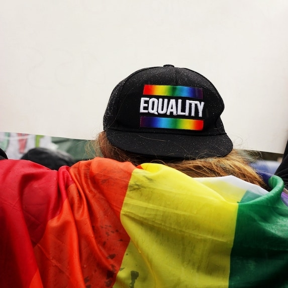 Person wrapped ina rainbow flag while wearing an
