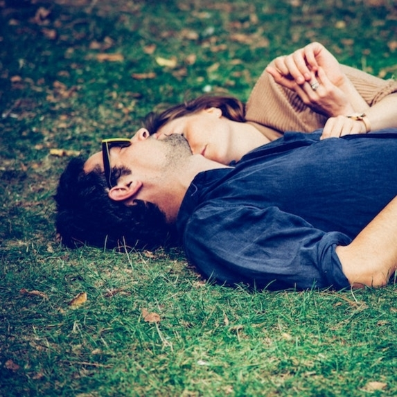 Couple lay down together in the grass