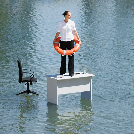 Woman standing on a desk surrounded by water