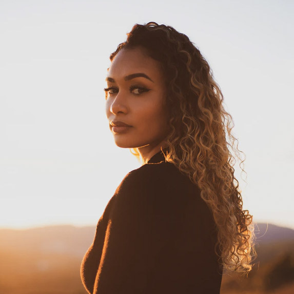 Beautiful woman standing in the sunset