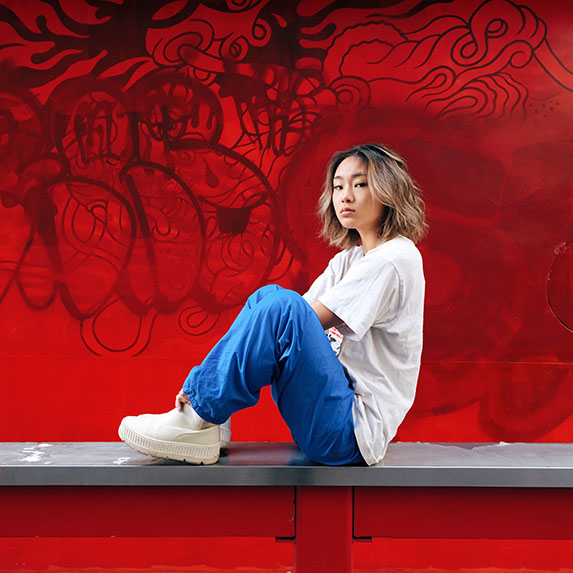 Asian girl sitting on a ledge