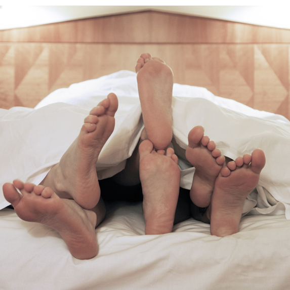 Three sets of feet poking out from beneath the covers at the end of the bed