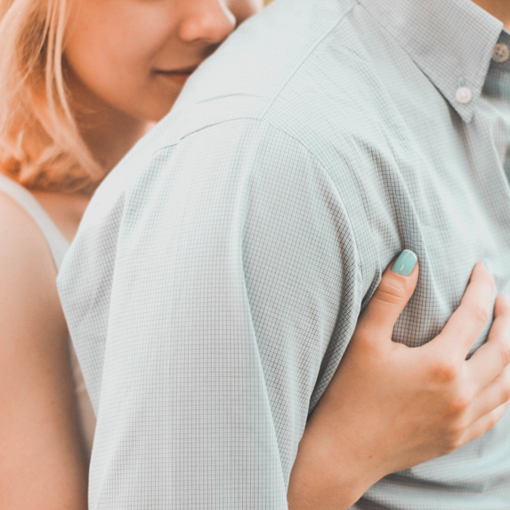 A young woman leans on her boyfriends shoulders and wraps her arms around his chest