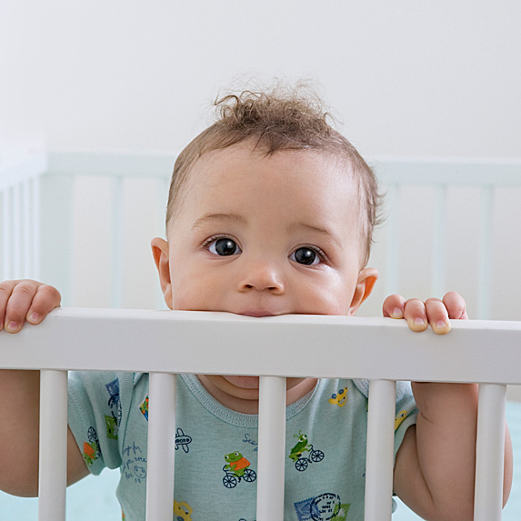 Baby in crib biting on railing