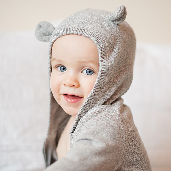 Baby wearing sweater with bear ears