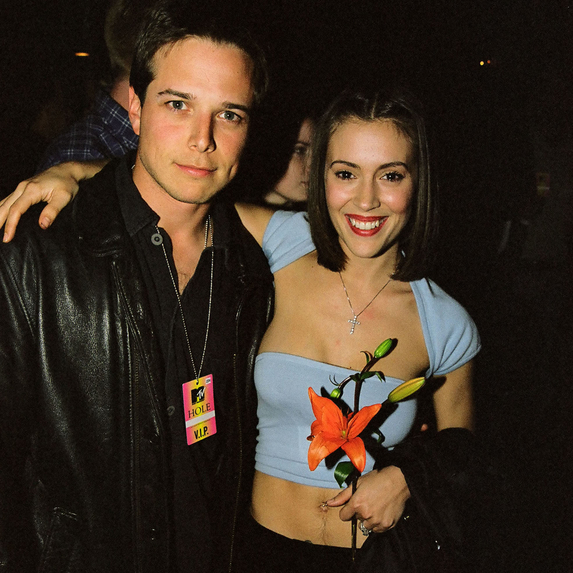 Scott Wolf and Alyssa Milano standing together at a Hole concert in 1999