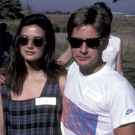 Demi Moore and Emilio Estevez in the '80s wearing sunglasses together while arm in arm